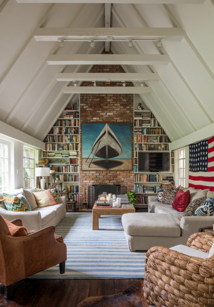 (8) In the cottage living room is the couple's book collection. Painting by Hamptons-based artist Terry Elkins. Custom sofa and sectional in Belgian linen, early Christopher Spitzmiller lamp, rug, and coffee table, all from Mecox.