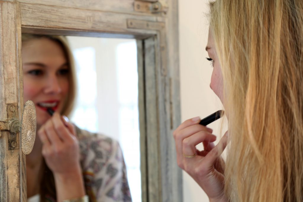 Lee applies her signature red lip.