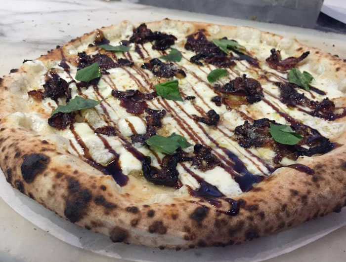 A pizza of the day at Pizaro's. Garlic, olive oil, crispy prosciutto and speck caramelized onions finished with a balsamic glaze. Photo courtesy Pizaro's Facebook Page.