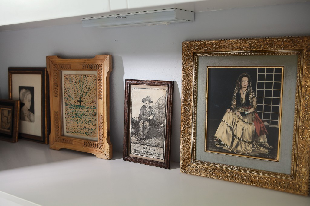 In a shelf in the guest bath, a lineup of favorite images holds court, including, far right, Cusack's paternal grandmother in fancy costume dress.