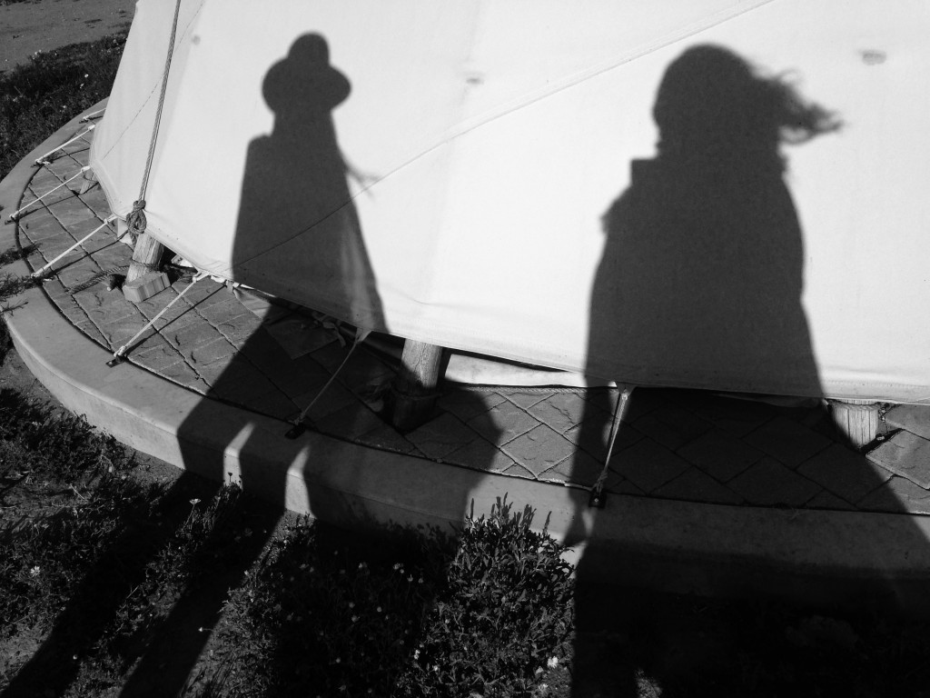 Our shadows against teepees at El Cosmico