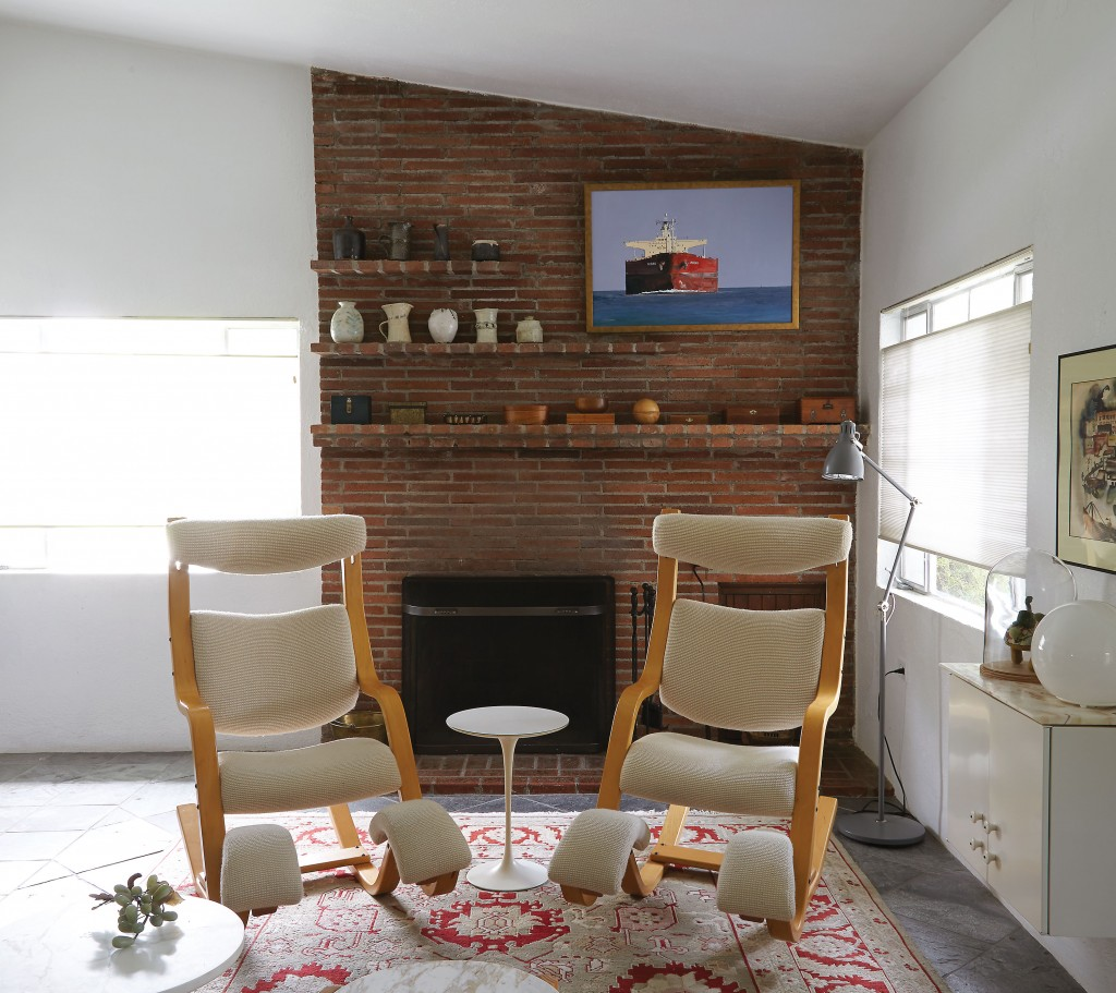 """In the living room, a pair of Gravity Balans chairs designed by Peter Opsvik in 1983 for Stokke with Knoll wool fabric and a Saarinen side table for Knoll, both from Reeves Antiques.  The oil painting over fireplace — titled """"Outbound"""" — is by Galveston Artist Leslie Sanders. The ceramics on the brick shelves were were made by Koush's mother."""