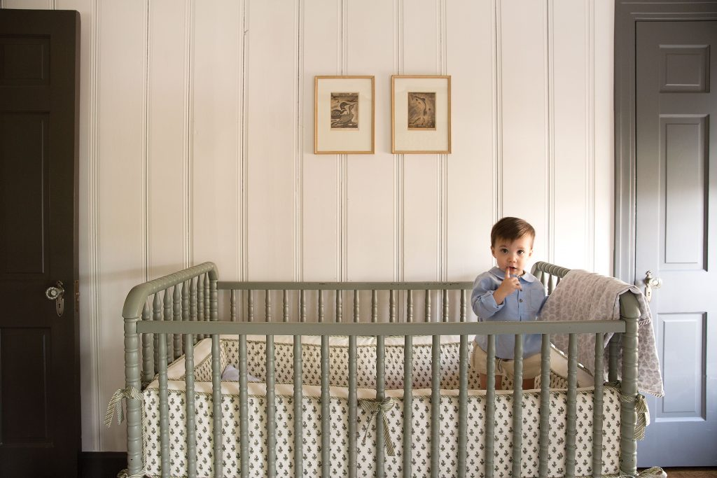 Theo awakes from his morning nap in a Jenny Lind crib with custom Mela & Roam bedding.