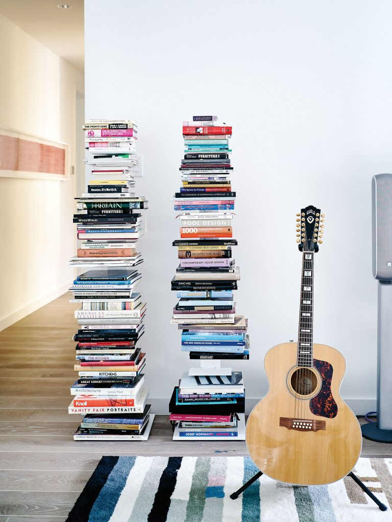"""In the sitting room, one of a pair of spruce and bird's-eye maple 12-string Guild guitars. Braun's favorite architecture and design books are stacked at the ready. In background, Makoto Sasaki's """"12 Hour Heartbeat"""" lithograph."""