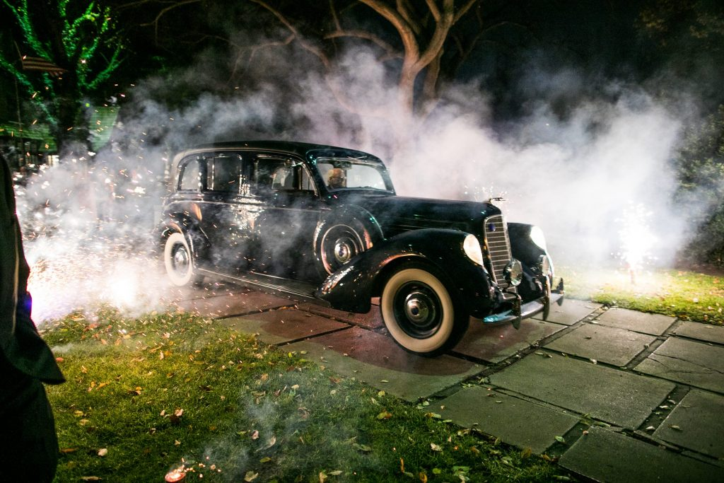 The bride and groom make their exit in a 1938 Lincoln Wiloughby Limousine — one of only five built