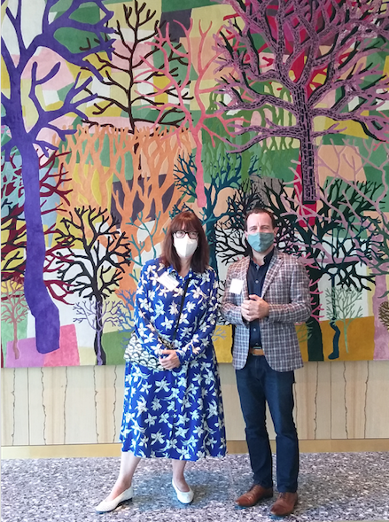 "MFAH curator Alison de Lima Greene and Jaime Odabachian of the artist-tapestry firm Odabashian pose in the MFAH future formal restaurant space, Le Jardinier, with Trenton Doyle Hancock's commission, ""Color Flash for Chat and Chew, Paris Texas in Seventy-Two,"" 2019-2020. (Photo by CDA)"