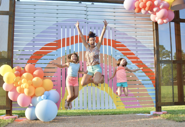 Mila, Anita, and Caroline Ticak are among the many neighbors excited by the Instagram possibilities of the latest Sugar & Cloth Color Wall at The Common, a reinvigorated shopping center on Pinemont. (Photo by Alex Montoya)